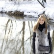 Smiling girl walking in winter forest - Foto Stock