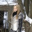 Smiling girl walking in winter forest - Stock fotografie