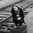 Girl sitting near railroad - Photo