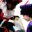 Zwarte Piet ( black pete) typical dutch character with young chi — Stock Photo #4052434
