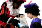 Zwarte Piet ( black pete) typical dutch character with young chi — Stock Photo