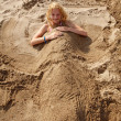 Girl buried under sand — Stock Photo