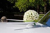 Wedding bouquet on white car — Stock Photo