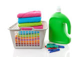 Laundry basket filled with colorful folded towels, pegs and bott — Stock Photo