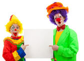 Two girl clowns holding empty text board — Stock Photo