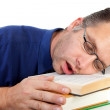 Male nerdy geek fall asleep with face on pile of books — Stock Photo
