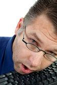 Male nerdy geek fall asleep on keyboard — Stock Photo