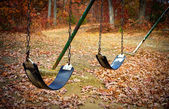 Old swingset at a park in the fall — Stock Photo