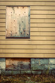 Boarded up windows in abandoned house — Stock Photo