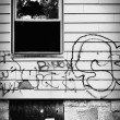 Stock Photo: Run down abandoned house with broken window and graffiti.
