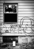 A run down abandoned house with broken window and graffiti. — Stock Photo