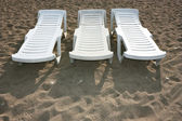 Wooden bench on sea beach sand — Stock Photo