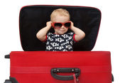 Little kid in sunglasses looking out red suitcase — Stock Photo