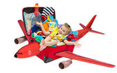 Little kid flying in travel suitcase packed for vacation — Stockfoto