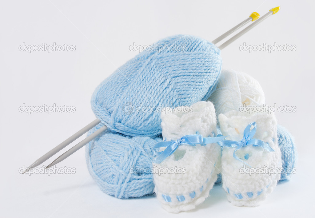 Knitted handmade baby's bootees, blue ball of yarn, needles. White background — Stock Photo #4880843