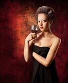 Woman with glass of red wine on grunge background — Stock Photo