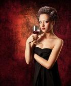 グランジ背景に赤ワインのグラスを持つ女性 — ストック写真