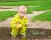 Child playing with ship in the puddle outdoor — Stock Photo