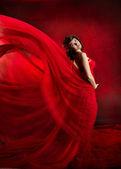 Beautiful woman in red flying waving dress. — Stock Photo