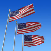 Three flags of USA against blue sky. — Stock Photo
