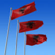 Three flags of Albania against blue sky. 3d illustration. - Stock Photo