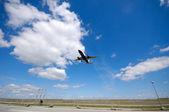 Low plane near airport — Stock Photo