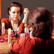 Beautiful young woman looking at mirror and putting make up — Stock fotografie