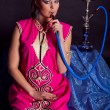 Woman in oriental outfit smoking water-pipe — Stock Photo