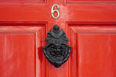 A red wooden door with a large Georgian door knocker — Stock Photo