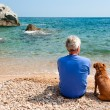 Man with his dog at the beach - Stock Photo