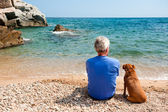 Man with his dog at the beach — Stock Photo
