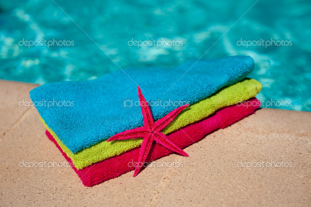 Colorful towels and starfish at the swimmingpool — Stock Photo #4125364