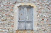 Antique door in brick wall — Stock Photo