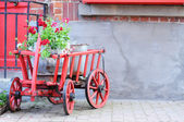 Old red cart with geraniums — Стоковое фото