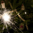 Stock Photo: Sparkler and Christmas tree