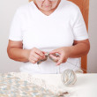 Elderly woman knitting - Stock Photo