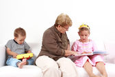 Reading and playing with granny — Stock Photo