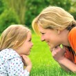 Young mother and daughter laying on the grass — Stock Photo