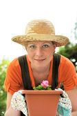 Young woman - gardening - potting Begonia — Stock Photo
