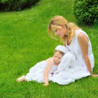 Young mother and daughter resting in meadow — Stock Photo