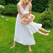 Young mother and daughter playing in meadow — Stock Photo