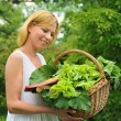 Young woman holding basket with vegetable — Stock Photo