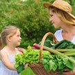 Young woman and daughter with fresh vegetable — Stock Photo