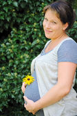 Pregnant woman holding her belly and yellow flower — Stock Photo