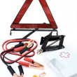 Emergency kit for car - first aid kit, car jack, jumper cables, warning tri - Stock Photo