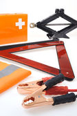 Emergency kit for car - first aid kit, car jack, jumper cables, warning tri — Stock Photo