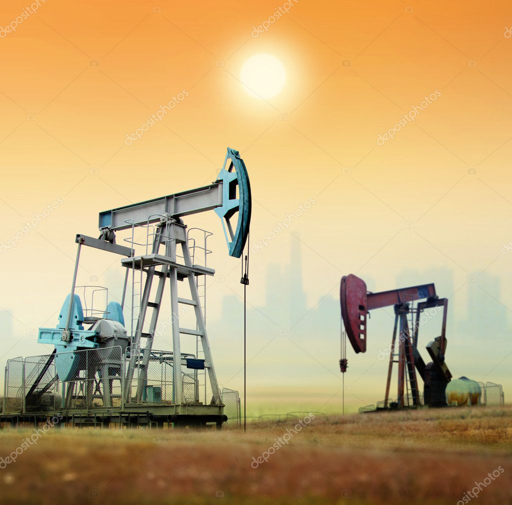 Working oil pumps in rural place against factory — Stock Photo #4412321