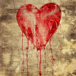 Stock Photo: Broken and bleeding heart on the wall