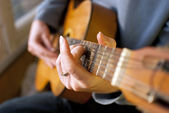 Hnědá kytara v rukou člověka, hraje to — Stock fotografie