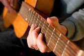 Brown guitar in hands of the guy playing it — Stock Photo